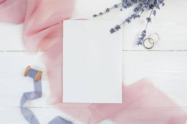 Fita branca cartão em branco com dois anéis de casamento
