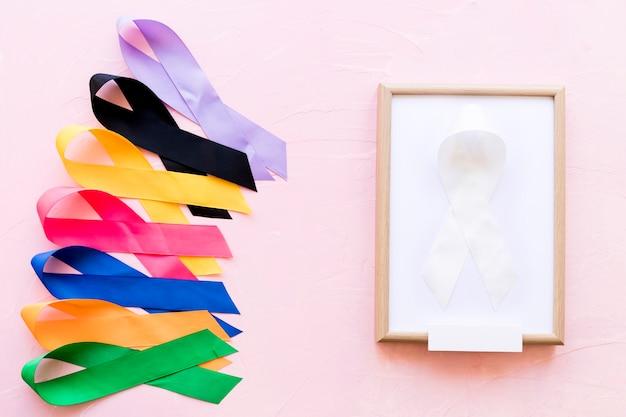 Fita branca em moldura de madeira branca perto da linha da fita colorida da consciência