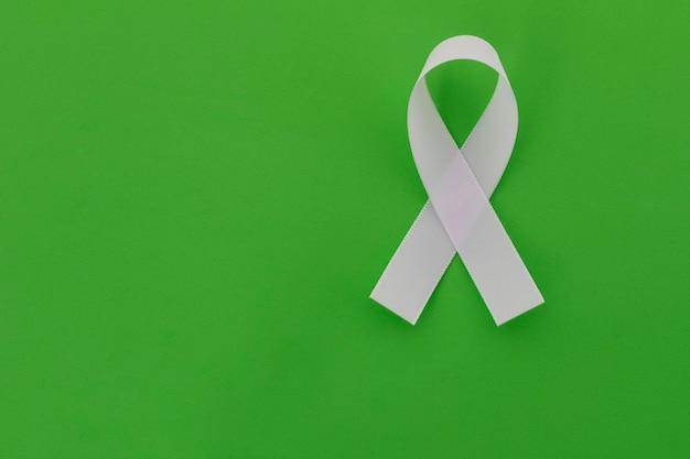 Fita branca sobre fundo verde, representa programa de prevenção de saúde mental. janeiro branco.