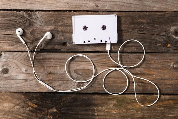 Fita cassete branca conectada com fone de ouvido na mesa de madeira
