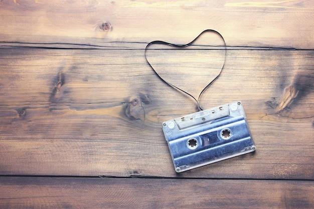 Fita cassete com fita em forma de coração em fundo de madeira