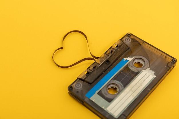 Fita cassete de áudio em fundo amarelo. filme moldando o coração, cartão postal do dia dos namorados. espaço vazio.
