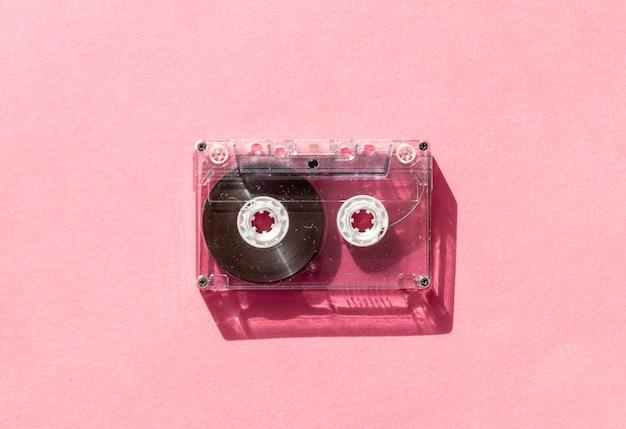 Fita cassete de áudio transparente retrô em fundo rosa. tecnologia da música vintage