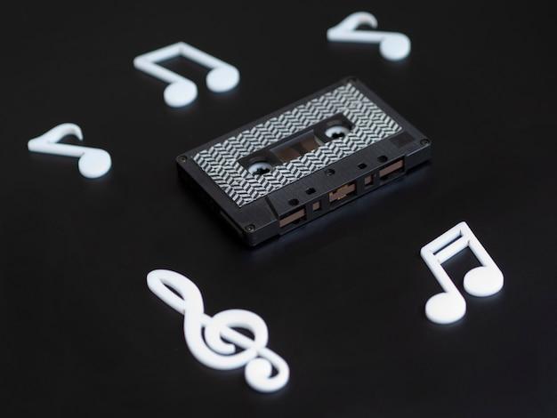 Fita cassete preta sobre fundo escuro com notas