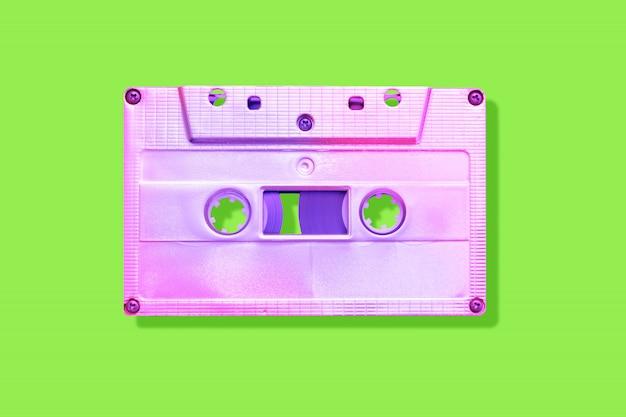 Fita cassete rosa neon sobre fundo verde com sombra