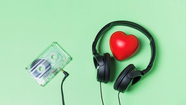 Fita cassete transparente conectada com fone de ouvido em torno do coração vermelho
