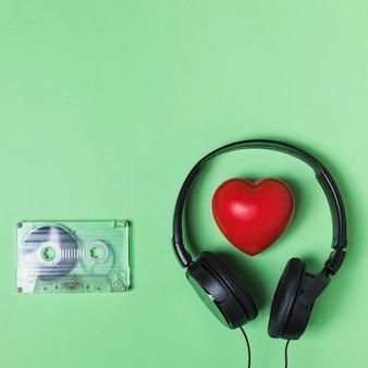 Fita cassete transparente; fone de ouvido e coração vermelho sobre fundo verde