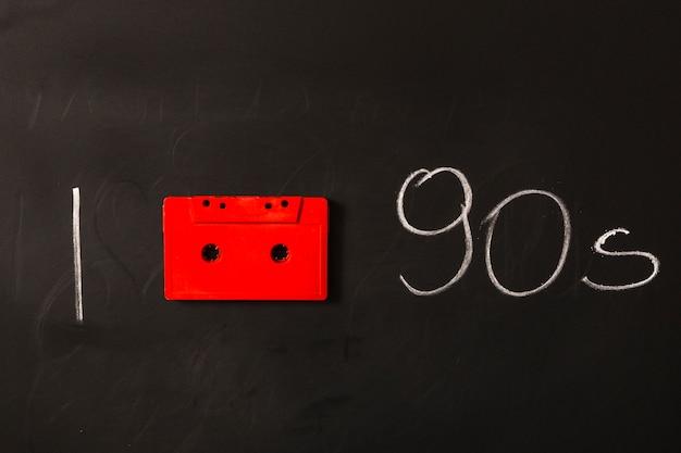 Fita cassete vermelha com anos noventa, escrita no quadro-negro