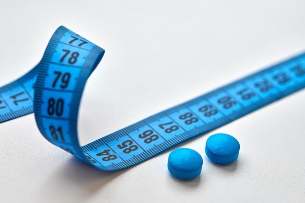 Fita centimétrica azul e pílulas dietéticas redondas isoladas