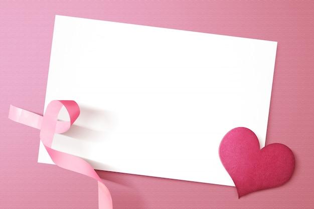 Fita coração e consciência-de-rosa com papel branco vazio