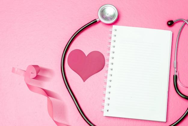 Fita coração e consciência-de-rosa com um estetoscópio e livro vazio