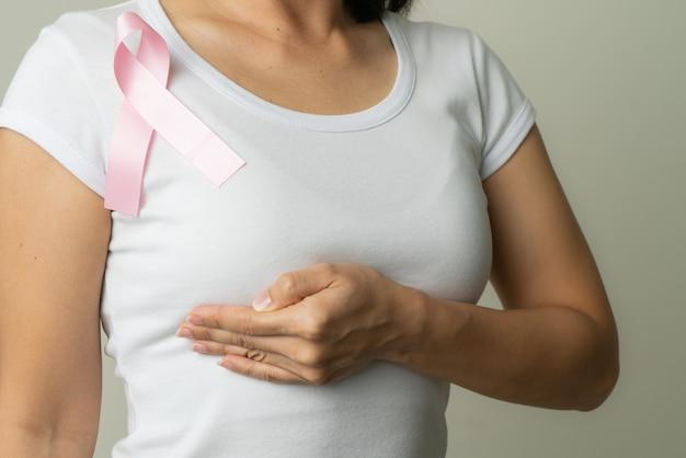 Fita crachá rosa no peito da mulher para apoiar a causa do câncer de mama. conceito de conscientização do câncer de mama