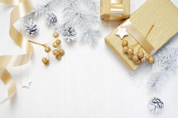 Fita de arco de ouro de presente de natal de maquete e cone de árvore, flatlay em um fundo branco de madeira.