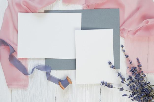 Fita de cartão em branco branco sobre um fundo de tecido rosa e azul com flores de lavanda