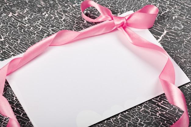 Fita de cetim com cartão em branco sobre fundo cinza