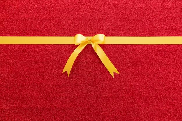 Fita de cetim dourada brilhante com laço em fundo colorido glitter vermelho