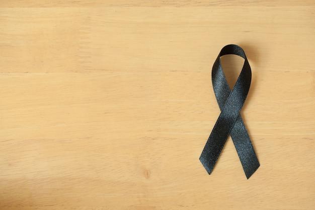 Fita de consciência negra em fundo de madeira. símbolo de luto e melanoma. costela