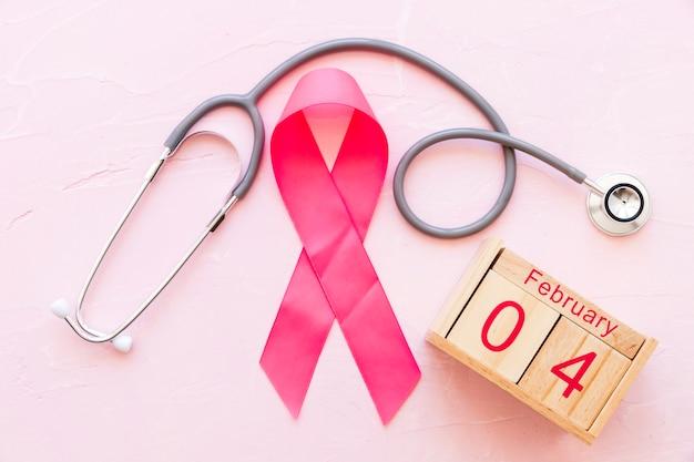 Fita de conscientização do dia mundial do câncer com estetoscópio e 4 de fevereiro caixa de madeira