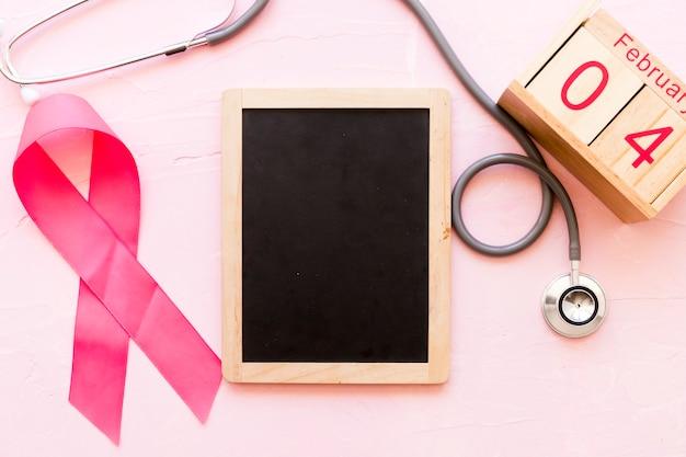 Fita de conscientização do mundo câncer dia com estetoscópio, ardósia de madeira e 4 de fevereiro caixa de madeira
