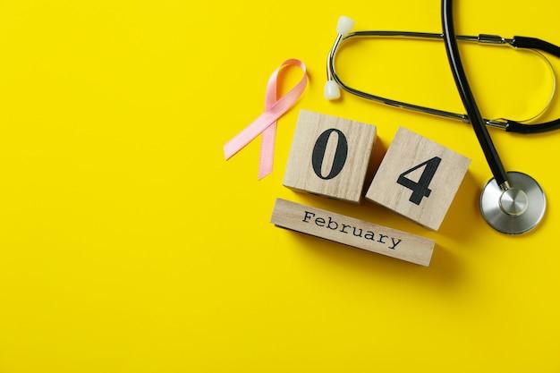 Fita de conscientização rosa, estetoscópio e 4 de fevereiro em fundo amarelo