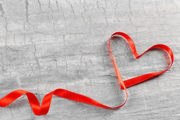 Fita de coração vermelha em plano de fundo texturizado cinza