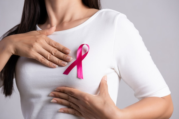Fita de crachá rosa no peito de mulher para apoiar a causa do câncer de mama. cuidados de saúde .