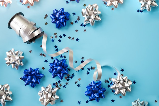 Fita de férias de natal azul e prata curva contra fundo azul. cartão de férias mágicas. fitas azuis brilhantes. laço festivo de fita