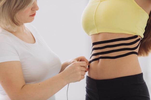 Fita de kinesio na barriga da mulher. jovem mulher caucasiana com fita terapêutica elástica de cinesiologia na barriga dela.