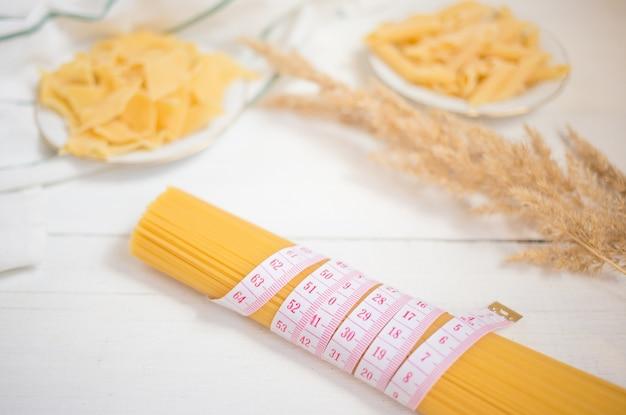 Fita de medição com grupo de espaguete italiano cru da massa, variedades de massa. dieta, conceito de comida saudável