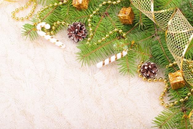 Fita de natal dourada, bolas e miçangas em galho de pinheiro verde