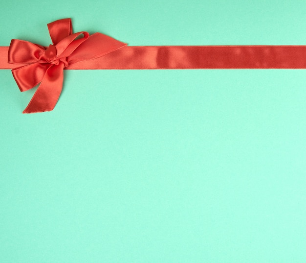 Fita de seda vermelha esticada e arco amarrado, fundo verde