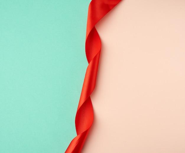 Fita de seda vermelha torcida em um fundo verde-bege