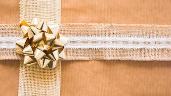 Fita de tecelagem decorativa e laço dourado em papel de presente