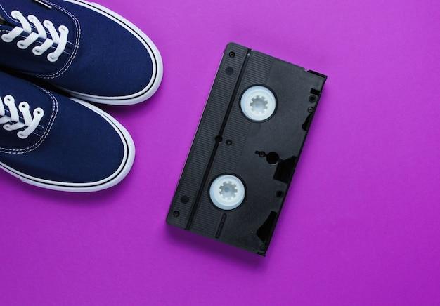 Fita de vídeo, jeans, tênis em fundo roxo