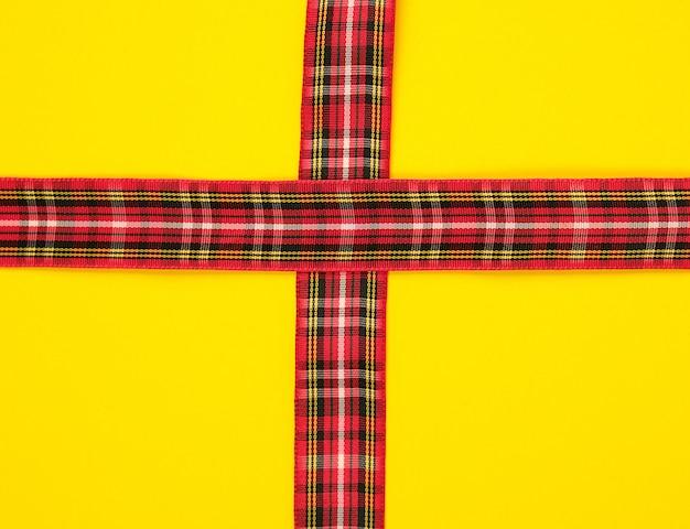 Fita decorativa vermelha em uma cruz de caixa em uma cruz