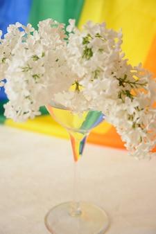 Fita do arco-íris lgbt e um buquê lilás branco em vidro. símbolo da fita de orgulho. copie o espaço. conceito de direitos lgbt.