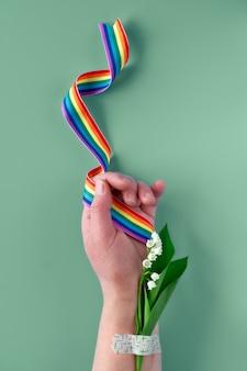 Fita do arco-íris na mão da mulher madura com flores de lírio do vale. bouquet anexado com remendo de assistência médica. obrigado médicos e enfermeiros do nhs!