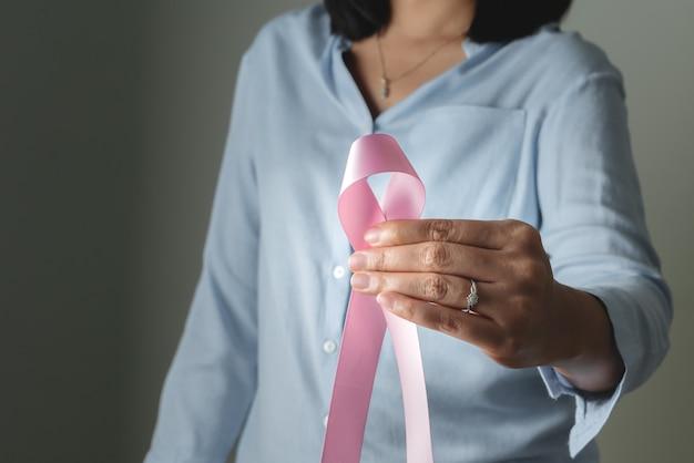Fita do crachá rosa na mão da mulher para apoiar a causa do câncer de mama. conceito de conscientização do câncer de mama