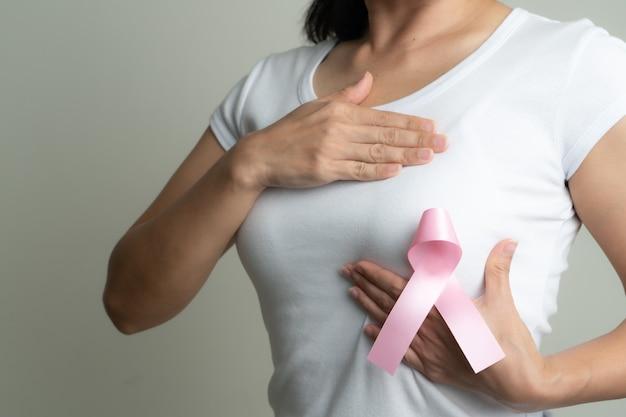 Fita do crachá rosa no peito da mulher para apoiar a causa do câncer de mama.