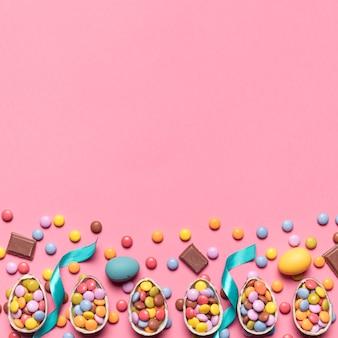 Fita; doces de gema e ovos de páscoa com espaço para escrever o texto no pano de fundo rosa