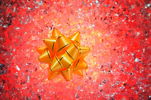 Fita dourada de presente de natal no gelo vermelho