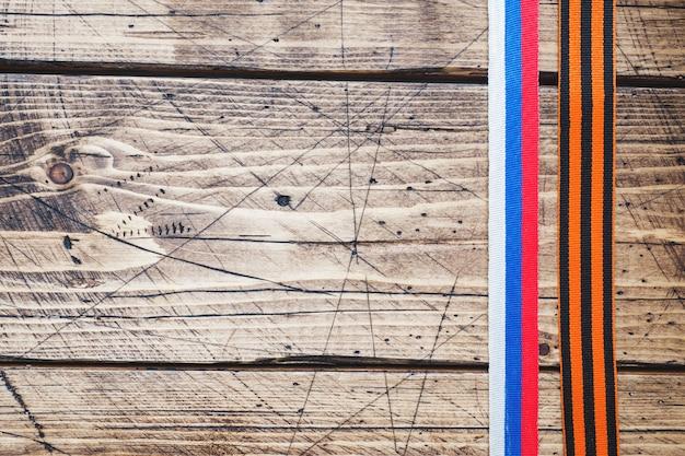 Fita e fita de george com a bandeira do russo tricolor no fundo de madeira.