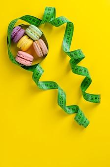 Fita e macarons de medição verdes no amarelo. copie o espaço. vertical