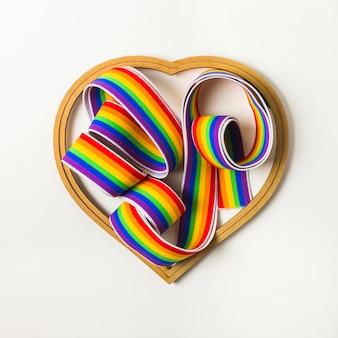 Fita em cores lgbt entre o símbolo do coração