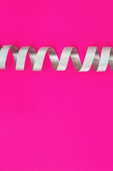 Fita espiral de prata no papel cor-de-rosa.