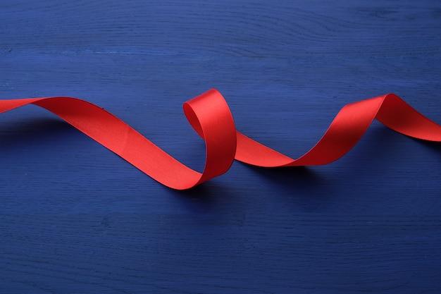 Fita fina de seda vermelha torcida sobre um fundo azul de madeira