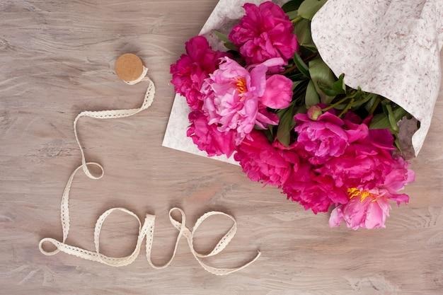 Fita formada na palavra amor com buquê de peônias