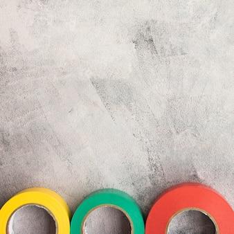 Fita isolante colorida em linha no pano de fundo concreto