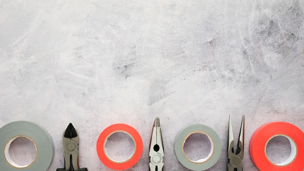 Fita isolante e alicate dispostos em linha em piso de concreto de cimento branco
