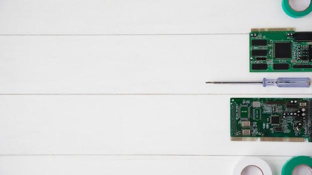 Fita isolante; testador e placa de circuito organizado na mesa de madeira branca